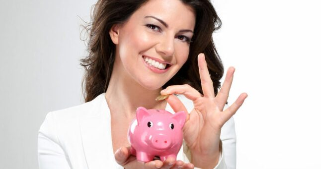 Young beautiful woman standing with piggy bank money box on white